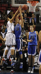 Huskies forward Moore blocks a shot by the Blue Devils forward Peters as Duke center Vernerey watches during the second half of their NCAA Philadelphia regional final college basketball game in Philadelphia