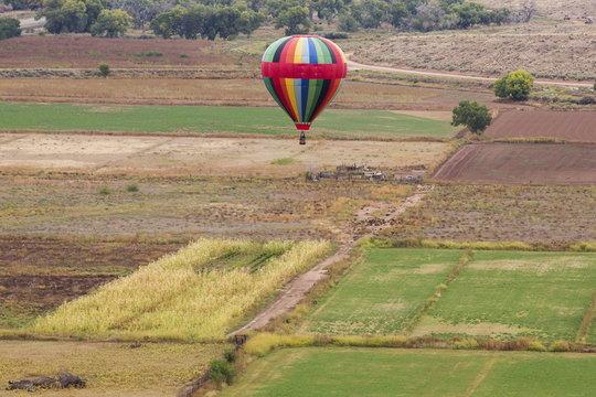 A hot air balloon floats over a field during the 2015 Albuquerque International Balloon Fiesta in Albuquerque, New Mexico