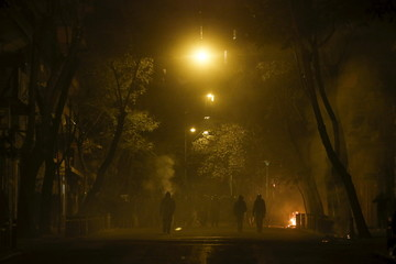Hooded youth walk amidst tear gas smoke during clashes with clashes with riot police in Athens