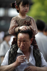 A man smokes as he carries a girl on his shoulders in downtown Shanghai