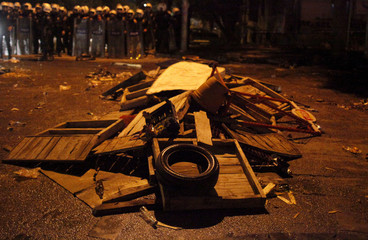 Riot policemen stand in front of a barricade during a demonstration by anti-government protesters in Kennedy street in central Ankara