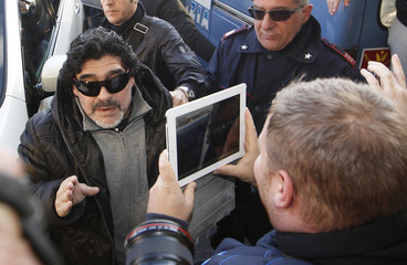 Argentine former soccer star Maradona is pictured with iPad as he arrives in Naples