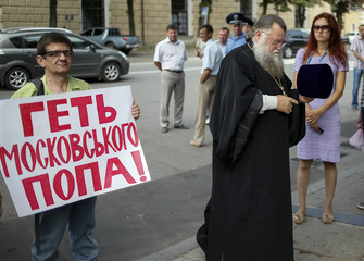 Protester holds a placard as a clergyman passes nearby, near the Kiev Pechersk Lavra monastery on the day of the election of the Primate of the Ukrainian Orthodox Church of the Moscow Patriarchate, in Kiev