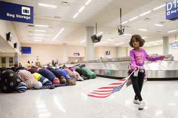 A young girl dances with an American flag in baggage claim while women pray behind her at Dallas/Fort Worth International Airport