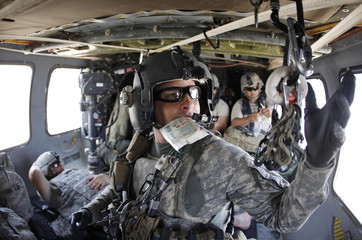 Staff Sergeant James Shields on board a medevac UH-60A Black Hawk helicopter from the 101st Airborne division, Task Force Destiny, prepares an infusion for a soldier wounded in the leg, while flying over Kandahar province