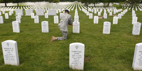 File photo of a U.S. Army soldier visiting a grave on 4th of July in Arlington National Cemetery in Virginia