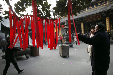 Visitors look at red prayer ribbons at the Longhua Buddhist Temple during Chinese Lunar New Year in Shanghai