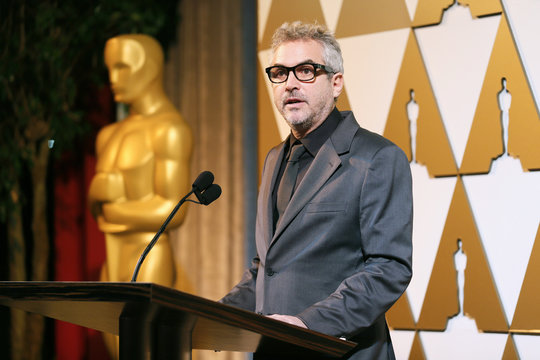 """Director Alfonso Cuaron presents director Paolo Sorrentino, whose Italian film """"The Great Beauty"""" is nominated in the Foreign Language Film category, with a nomination certificate at the 86th Academy Awards Foreign Language Nominee Reception at Ray's and"""