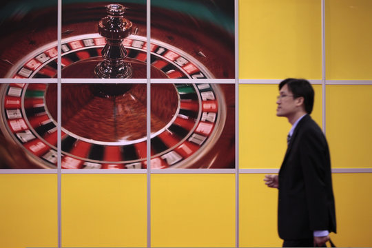 A man walks past a billboard displaying a roulette wheel during the Global Gaming Expo Asia in Macau