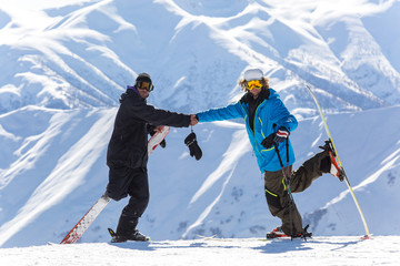 Two skier shake hands during descent at a ski resort. Beautiful winter landscape with snow-topped mountains.