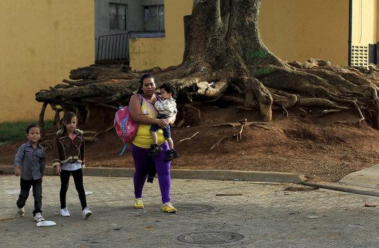 Hazel Castillo walks with her children to an aerobics class in Los Guidos de Desamparados