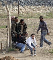 Syrian refugees try to cross the border fence from the northern Syrian town of Ras al-Ain into Turkey during an air strike on Ras al-Ain, in the Turkish border town of Ceylanpinar