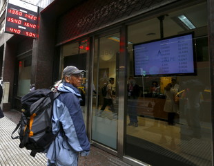 Pedestrian looks at currency exchange rates board at a money exchange in Buenos Aires' financial district