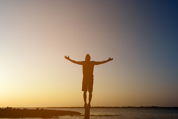 Silhouette man with hands rise up,standing on peak open arms on the pillars at the river, enjoying nature the sun concept world wisdom fun hope