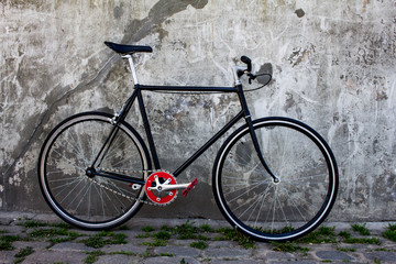 black hipster bicycle near the grey concrete wall