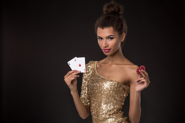 Woman winning - Young woman in a classy gold dress holding two aces and two red chips, a poker of aces card combination.