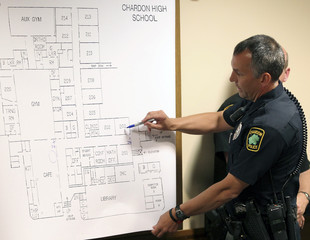 Chardon police officer Matt DeLisa circles the areas where he found the bodies of wounded people who were shot by suspected gunman TJ Lane on a Chardon High School floor plan in court in Chardon