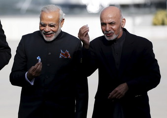 India's PM Modi and Afghan president Ashraf Ghani hold sweets as they inaugurate Afghanistan's new parliament building, which was built with the Indian government's financial assistance, in Kabul