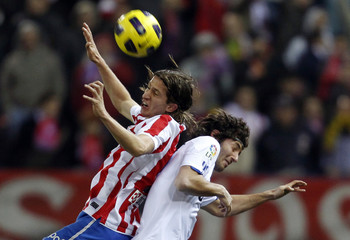 Atletico Madrid's Luis and Real Madrid's Granero goes up for the ball during their match at the Vicente Calderon stadium in Madrid