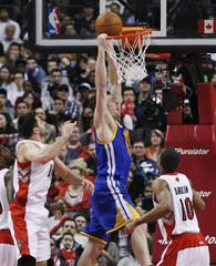 Warriors' Lee misses a slam dunk against Raptors' Kleiza and DeRozan during their NBA basketball game in Toronto