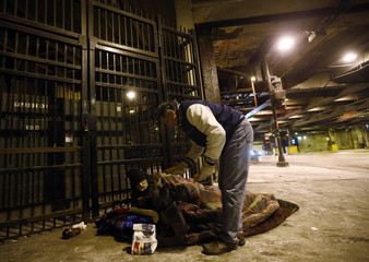 Doctor Angelo checks on a homeless man under the overpasses on Lower Wacker Drive in Chicago
