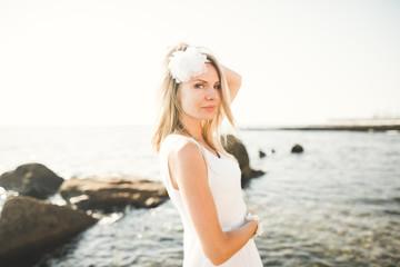 portrait of young woman posing near sea, wearing a dress