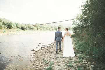 Beautifull wedding couple kissing and embracing near the shore of a mountain river with stones