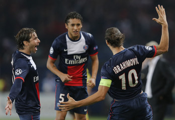 Paris Saint-Germain's Ibrahimovic celebrates with team mates Marquinhos and Maexwell after he scored against Benfica during their Champions League soccer match in Paris