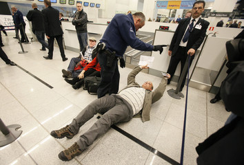 A would-be passenger lays on the ground as around 100 pro-Palestinian activists stage a protest at Brussels national airport in Zaventem