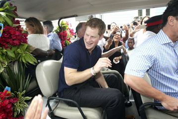 Britain's Prince Harry smiles as he sits in a specially decorated golf buggy during a tour of Harbour Island in Nassau