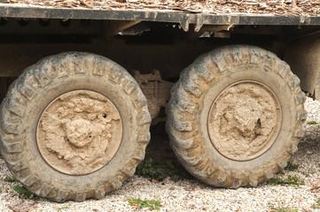 Muddy grunge tyre wheels of heavy duty truck closeup