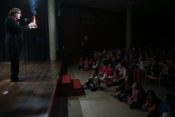 Children from the shanty town settlement of El Gallinero watch a magician perform before receiving presents from the Three Wise Men during a distribution of donated toys in Madrid