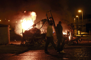 People walk past a burning double-decker bus, which was hijacked and set alight by loyalists, in Belfast