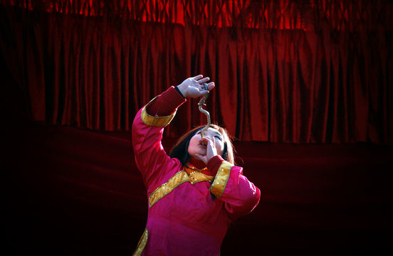 A woman swallows a live snake as she performs on a small stage showcasing acts of magic and feats of unusual physical abilities at the temple fair in Ditan Park