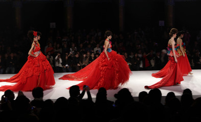 Models present creations from designer Tsai Meiyue's Spring/Summer 2012 wedding dress collection during China Fashion Week in Beijing