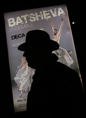 A man is silhouetted against a poster of Israel's Batsheva Ensemble dance group as he queues to attend a performance by the dance group at Sadlers Wells Theatre in London