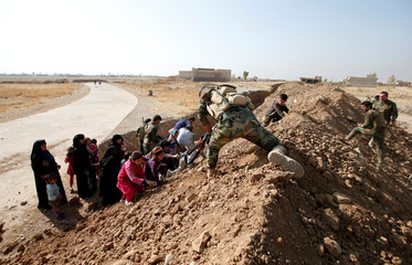 Kurdish Peshmerga fighters help Iraqi women and children climb over a berm as they were escaping the Islamic State controlled village of Abu Jarboa at the frontline