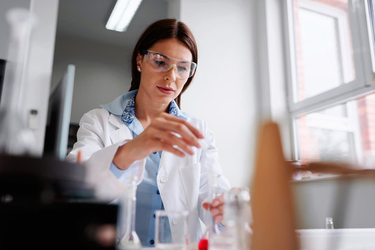 Woman scientist carrying out experiment in research laboratory