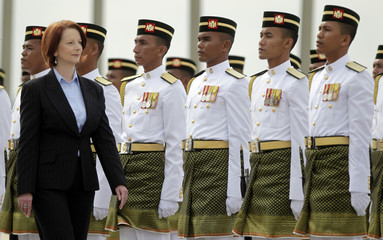 Australia's Prime Minister Julia Gillard inspects an honour guard during a photo call outside the Prime Minister's office in Putrajaya