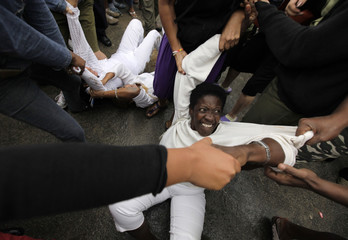 Security forces drag members of the Ladies in White into a bus after a march in Havana
