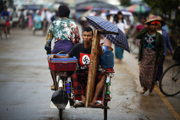 Zaw Lin Tun wears a t-shirt with the Nazi swastika sign as he rides on a rickshaw to a ferry port in Dallah Township outside Yangon