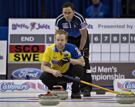 Sweden skip Edin watches the line of a shot as Scotland skip Murdoch watches from behind, during their page playoff game at the World Men's Curling Championships in Victoria