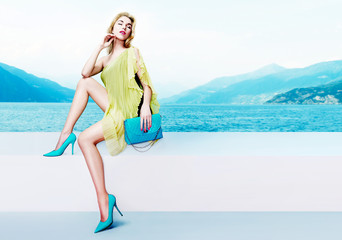 Beautiful blond hair woman sitting on the lake side. Wearing the yellow dress, sky blue shoes and purse.