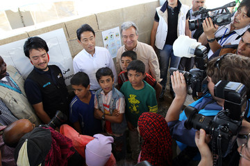 Kishida and Guterres pose with young refugees during their visit at Al Zaatri refugee camp