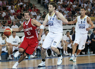 Kerem Tunceri of Turkey drives past Fabricio Oberto of Argentina during their FIBA exhibition basketball game in Ankara