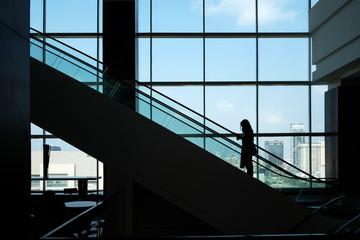 Women walk up the escalator in Silhouette.