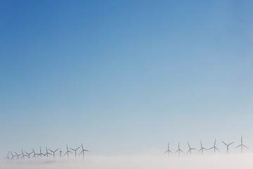 Fog partially covers wind turbines on a hill near Tudela