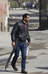 A plainclothes security personnel takes his position during clashes with Al-Azhar University students who support the Muslim Brotherhood and deposed President Mursi, at the university's campus in Cairo