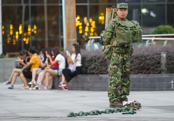 A man dressed in camouflage clothing sells toy soldiers on a street in Guangzhou