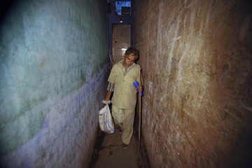 Javed Sheikh carries dead rats in a plastic sack through an alley in a slum area on the outskirts of Mumbai